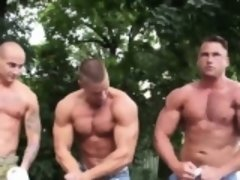 Three muscled hunks arm wrestling in the street