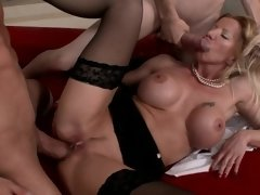 A girl with large tits is doing a double blow job to her partners