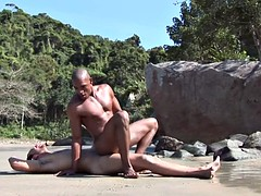 Ebony stud with six pack on the partner's cock in the sand